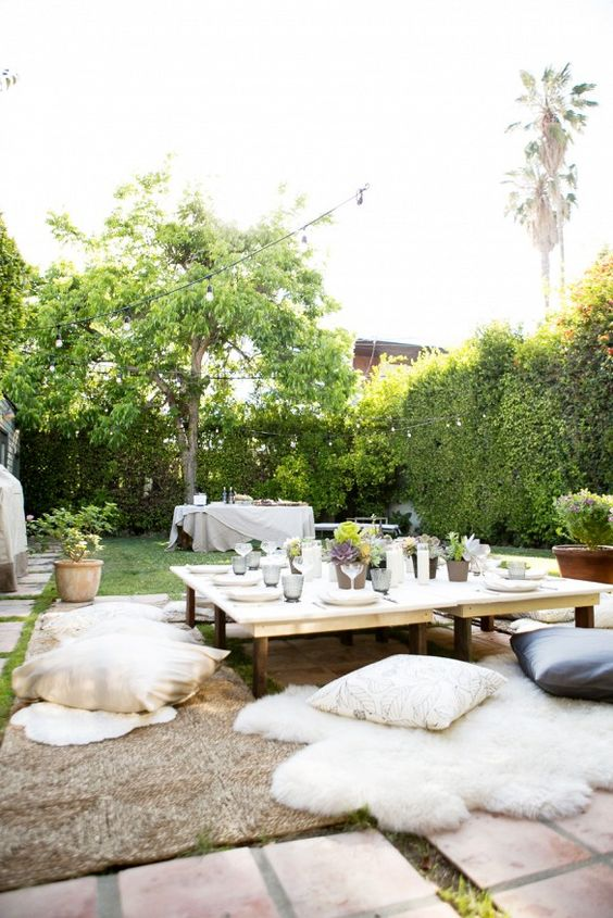 Outdoor dinner party setup with wooden tables, pillow seats, string lights and a buffet table.: