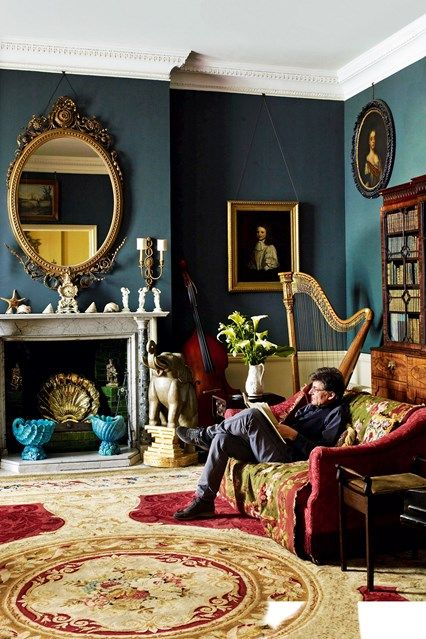 The music room at Faringdon House is hung with portraits and painted a rich green-blue.