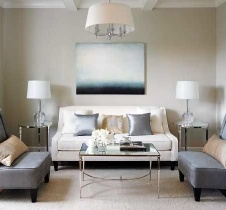abstract art, polished chrome drum pendant, french mirrored coffee table, white curvy sofa, gray slipper chairs, crystal lamps, mirrored accent tables, silk gray pillows and gold pillows.