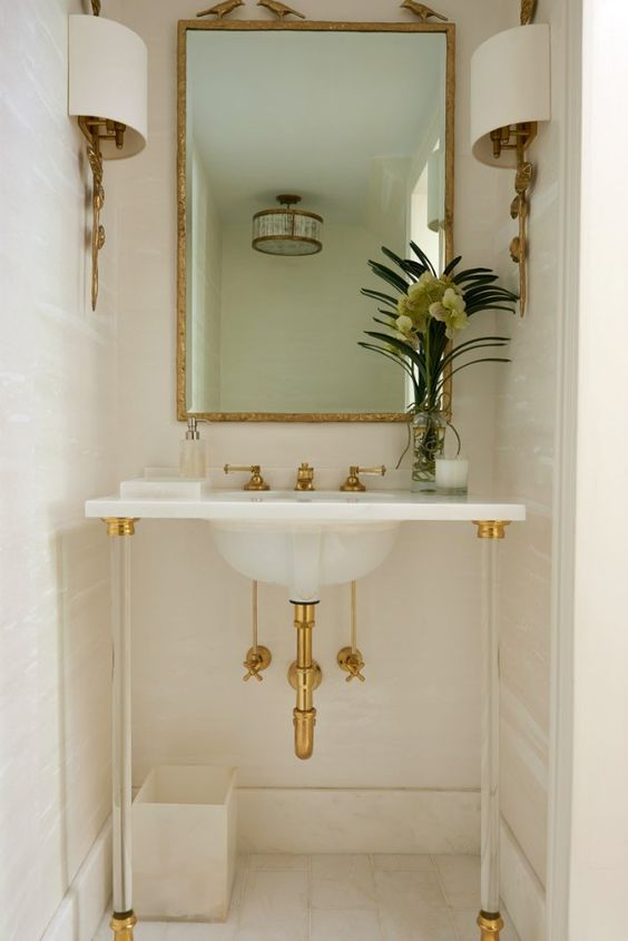 Contemporary half bath | Greenwich-based design and furnishings studio Lillian August shows just how much style can be squeezed into a small space. The sleek sink, soft palette, and gilded accents come together in a narrow nook that's perfectly functional and oh so pretty.