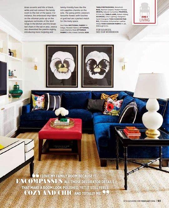 blue sofa with nailhead trim, large prints, carpet