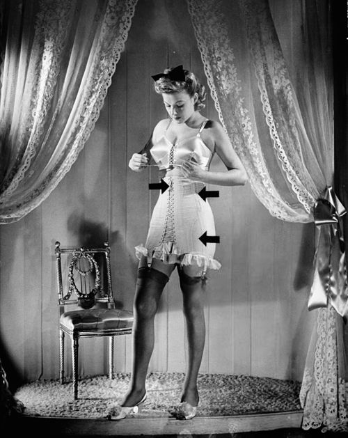 """Model showing how to lace a corset w. arrows pointing at spots where laces begin & end now that elastic & zippers have """"gone to war"""" as the WPB's (War Production Board) jettisoning of amenities is put to consumers. Photo by Nina Leen, 1942"""