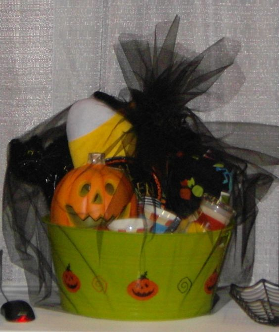 halloween raffle basket in large plastic tub with halloween themed decor  cocktail mixes  spooky