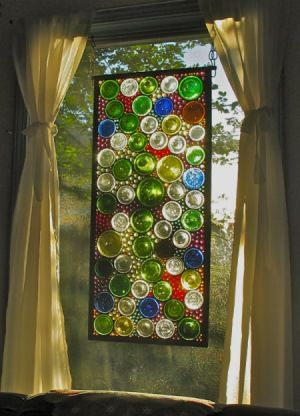 """Wine Bottles Used In Stained Glass At Thrifty Fun, the artist wrote, """"I work with stained glass a lot and often use the bottoms of wine bottles in my windows. The bottles with the pushed in bottoms look really cool with the sun shining through. It's a fair bit of work to get the bottoms cut and shaped for use, but well worth it.""""  To DIY, instructions are available  on YouTube."""