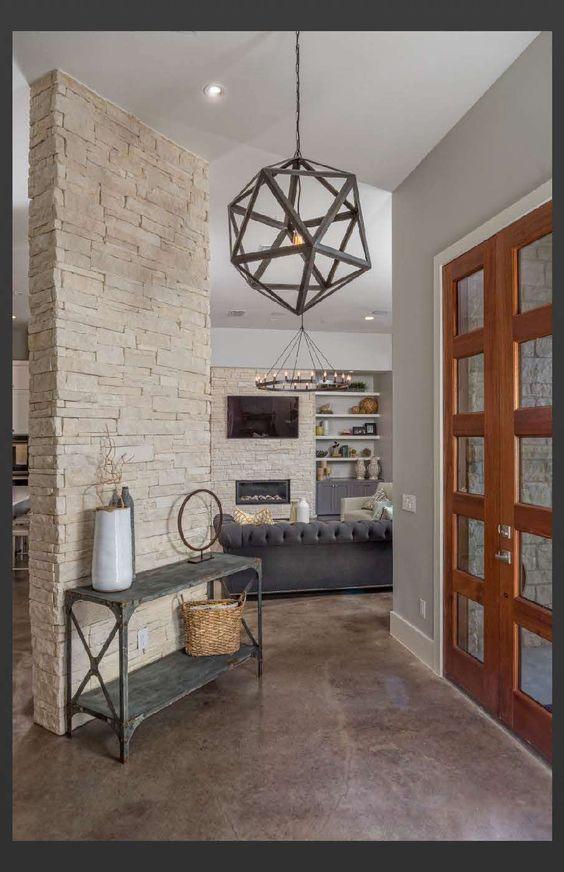 Stonewall Ridge | New Construction | Greenbelt Construction | Austin TX Custom Home Builder | www.GreenbeltConstruction.com Entry, stained concrete, concrete floor, pendant lighting, hanging chandelier, geometric chandelier, wood front door, stone wall