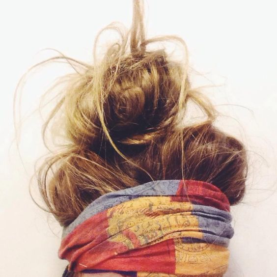 A messy top knot uses a scarf tied at the edge of her hairline to