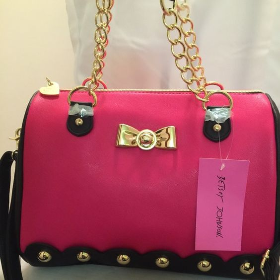 New Betsey Johnson Pink and Black Bowler bag Cutest bag ever. Brand new with tags never worn Betsey Johnson bowler bag. Gold hardware. Big round gold studs at the bottom of the bag. Bag is Fuschia and black. Black ruffle pattern lining. Gold chain handles. Shoulder strap. Interior cute Betsey pattern with hearts. Best part is the faux turn lock bow in the center. Zip closure. Heart on zipper. Size 12L6.5W9D. Price firm new bag✅✅ Betsey Johnson Bags