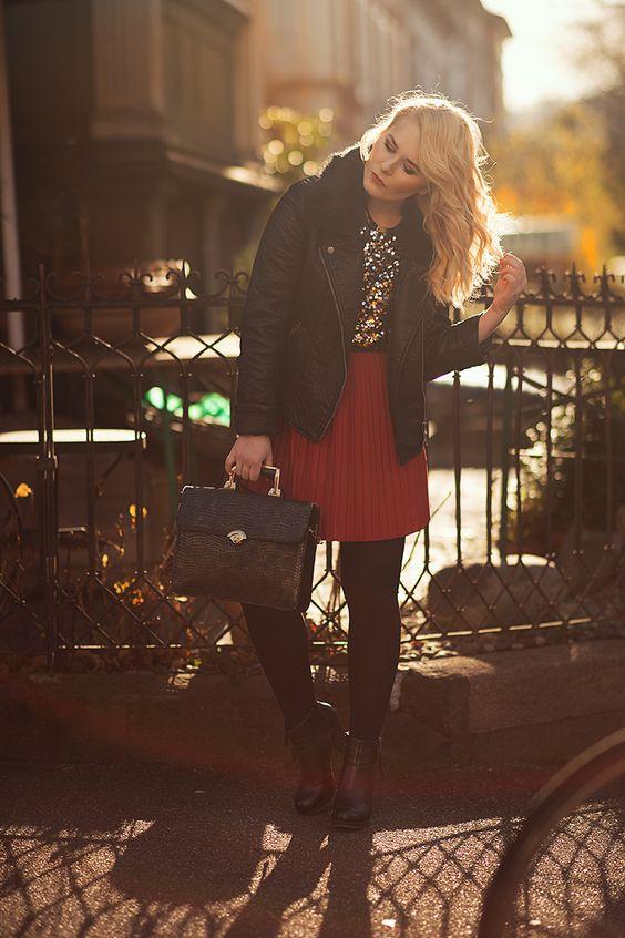 Christina Key trägt einen roten Plisseerock und eine schwarze Lederjacke