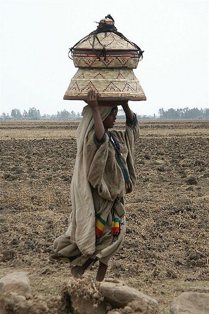 Africa | Girl carrying basket on her head; used as a table and as a recipient to transport the food.  Ethiopia. | © Eric Lafforgue: