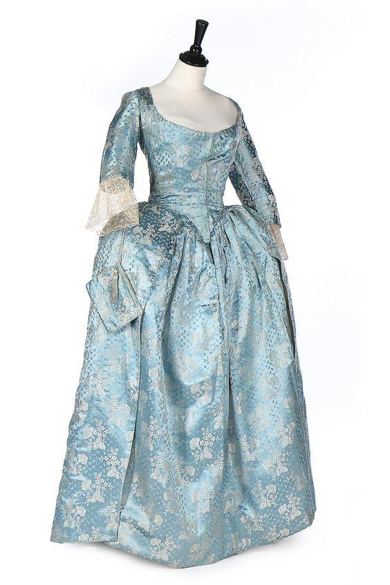 Robe à l'Anlgaise, 1760s, 19th century alterations. Tourquoise-blue silk satin, woven with mentoring white blossom, the ground figured with leaf sprigs.