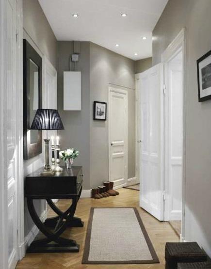 Pasillo en tonalidad gris en contraste con rodapie y puertas en blanco