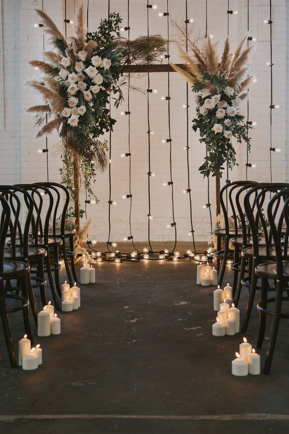 floral wedding arch with pampas plumes and festoon lights