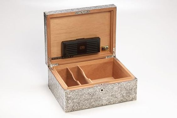 Sterling Silver Humidor     Silver King Exclusive; fully handcrafted and hand engraved humidor with an antique finish. Features sterling silver corners, hinges and key. Crafted on a hand made cedar humidor from Daniel Marshall.