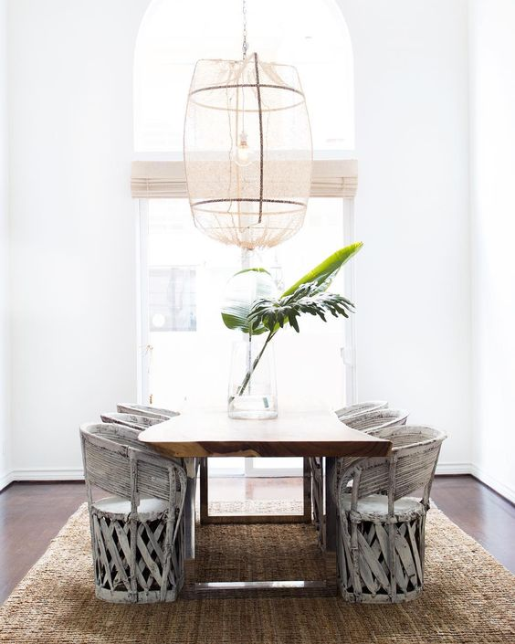 A dining room designed by Leanne Ford with minimal vintage style, rustic barrel chairs, rustic wood chunky dining table, dramatic pendant, and simple palm branch in clear glass vase. #diningroom #minimaldecor