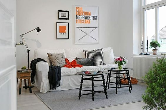 Check out this Scandinavian living room @desiretoinspire, where a white EKTORP sofa is accessorized with textured pillows and throws in black, gray and orange.