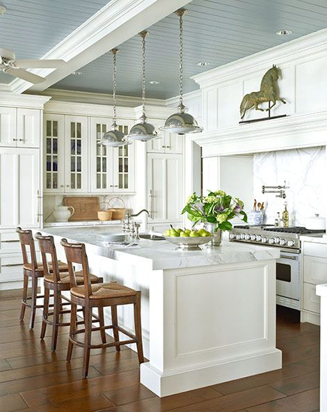 A blue-gray painted ceiling emphasizes the lakeside location of the home in which this white kitchen resides. Thick white marble countertops, marble backsplashes, and classic white cabinets draw attention to the room's main ornamentation: a horse weather vane galloping above the range. Dark-stained hand-scraped walnut floors provide an earthy foundation.
