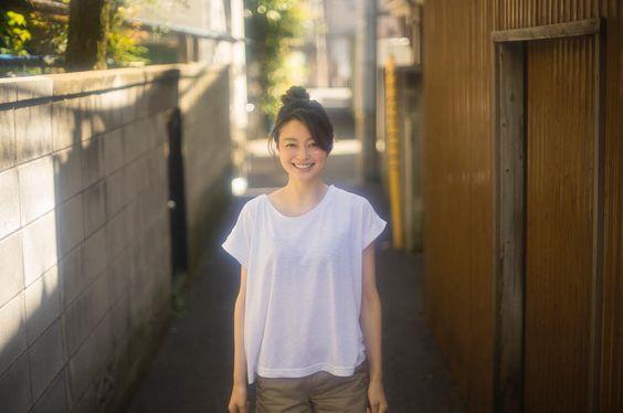 ドルマンの白いTシャツを着て路地に立っている小林涼子の画像
