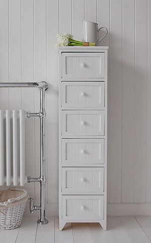 Tall slim bathroom storage furniture with 6 drawers for storage. A crisp white freestanding cottage bathroom storage furniture. A narrow bathroom cabinet with 3 drawers, each with a white wooden knob and tongue and grrove front. It is a Shaker style cabinet, elegant in simplicity, functional and durable. A timeless style for any bathroom.