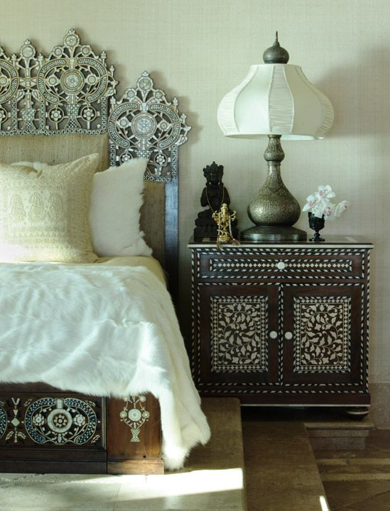 ource: Martyn Lawrence-Bullard Design  Ornate, bone inlaid nightstand and bed! Simple faux fur throw, paisly pillow and textured cream wallpaper. Beautiful metal lamp, Asian statues and orchid arrangement.