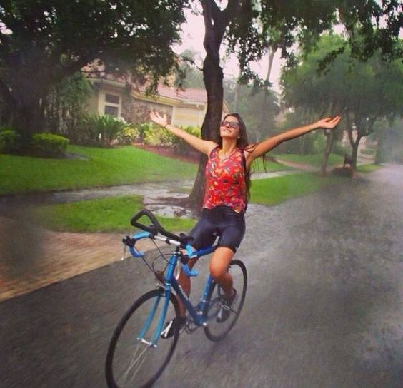 She rides, enjoying the down pour of the rain.