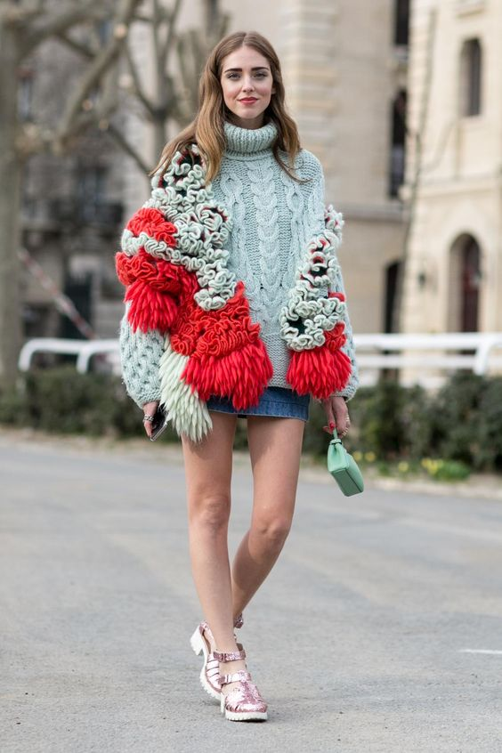 30 Perfect Oversized Sweater Outfit Ideas - Chiara Ferragni wearing a deconstructed knit turtleneck sweater with fringe, styled with a denim skirt and pink metallic shoes