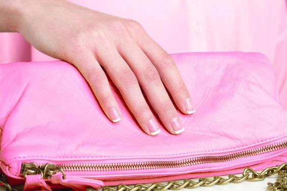una mano esmaltada con manicura francesa sobre un bolso rosa
