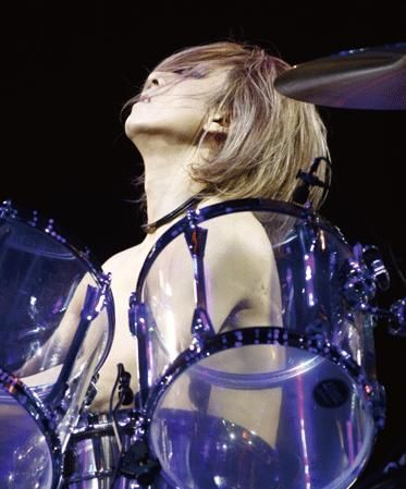上半身裸でクリアなドラムを叩いているXJAPAN・YOSHIKIの画像
