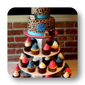 """This two tier leopard print baby shower cake topped a cupcake tower filled with coordinating bright pink, bright blue and white cupcakes in leopard print cupcake liners. The cake itself was topped with a handmade edible character of the """"mommy to be"""", accompanied by a baby buggy and personalized shopping bags."""