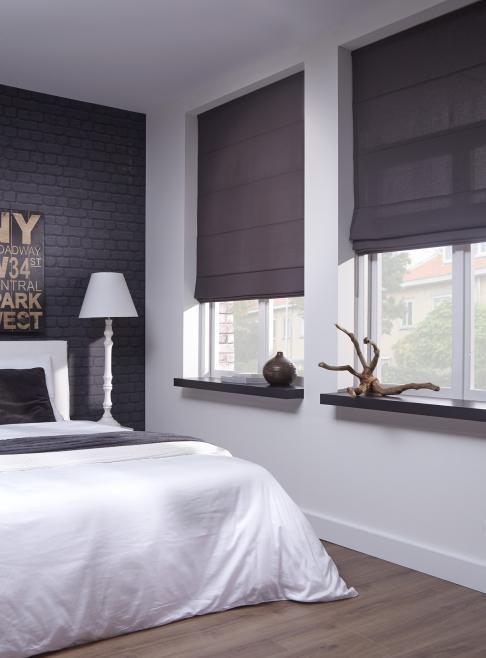 Houten vloer, witte muren, zwarte vensterbanken en bruine vouwgordijnen.