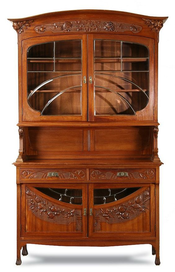 """19th century French Art Nouveau walnut vitrine, with flared cornice supported by carved pomegranates, over a relief carved frieze of grapes and pomegranates surmounting leaded and beveled glass upper doors, over a base cabinet with similar leaded and beveled glass inserts on the lower doors also with relief carved branches of pomegranates, 96""""h x 58""""w x 23""""d."""