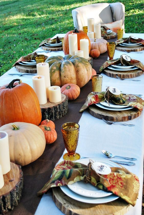 Layered fall tablescape with wood rounds, vintage floral napkins, pumpkins, and candles.