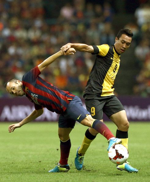 Andres Iniesta of Barcelona FC is tackled by Safiq Rahimi of Malaysia during the friendly match between FC Barcelona and Malaysia at the Shah Alam Stadium on August 10, 2013 in Kuala Lumpur, Malaysia.