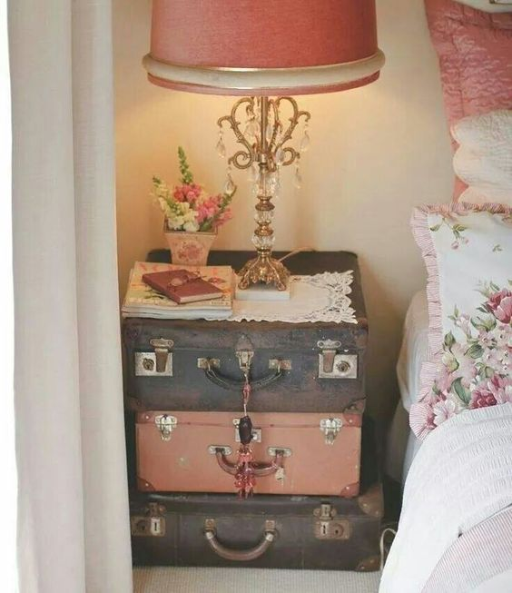 Vintage stacked suitcases used as a bedside table.