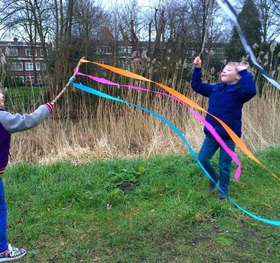 Buiten spelen met de wind en crêpe-papier slingers aan een stok. @Oermonumenten