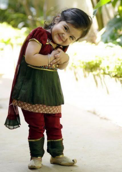 Indian baby girl. Her smile and costume is so lovely. She wears a Indian traditional clothes: