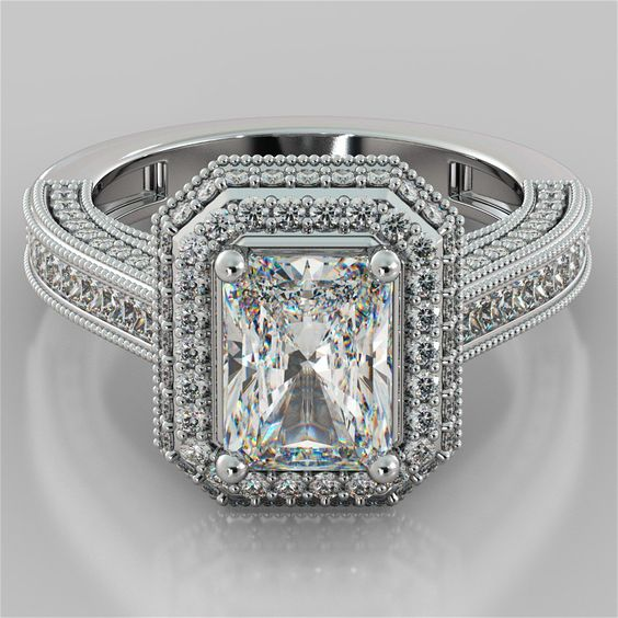 Old-World flair and elegant looks add to the dramatic style of this Radiant Cut Engagement Ring intricate patterns of milgrain borders that accentuate the stunning center stone in a double tier halo. <br /> <br /> Made to order in your choice of precious metal this Radiant Cut Engagement Ring comes as pictured with a 1.50Ct Radiant Cut simulated diamond and 1.28Ct in side stones. (Total Carat Weight: 2.78 CTW). <br /> <br /> A contoured Matching Band with an additional .94Ct in Side Stones…