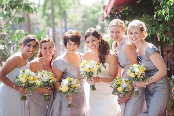 bridesmaids laughing in grey dresses with yellow flowers at loring pasta bar minneapolis