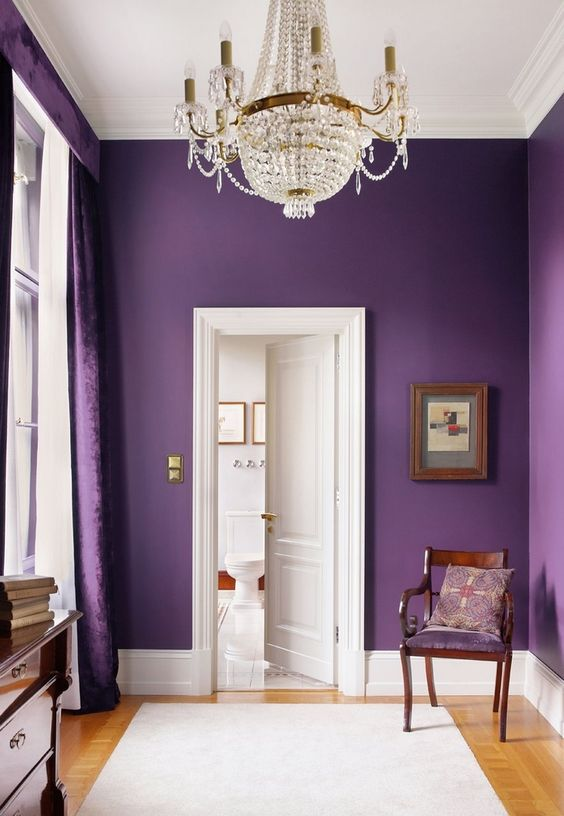 Dramatic, deep purple walls that draw attention to the crisp white high ceilings and glass chandelier. | 4inspireddesign.com