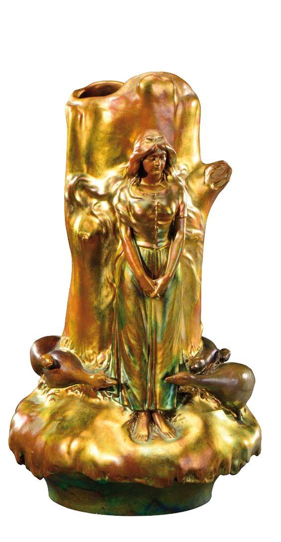 Zsolnay Pécs Vase en céramique émaillée irisée verte à nuance jaune orangé à panse renflée et col droit à décor en haut relief d'une bergères et d'oies à ses pieds. Signé du cachet aux cinq églises et numéroté. Vers 1900. H : 42,5 cm 15/5,8eE