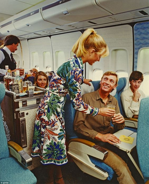 A stewardess hands a passenger a drink on a Qantas 747 in 1983. My uniform!! The golden days!