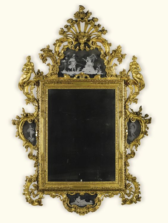 An Italian carved giltwood mirror, Venetian, mid 18th century with a rectangular bevelled plate within a leaf and scroll carved frame surmounted by an etched mirror cresting ornamented with classical figures carved with a stylised shell, flowers, mask and scrolls flanked by nereids, the apron and sides ornamented with conforming mirror plates, similarly ornamented with classical figures