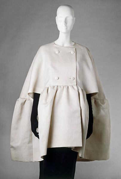 Evening cape | Cristóbal Balenciaga (circa 1963) This evening cape by Cristóbal Balenciaga (1895–1972) is made from white gazar. It is double-breasted with four covered buttons and has a deep flounce seam and inset pocket in the flounce. It was designed to be worn with matching dress and is typical of the pared-down elegance of his creations of the 1960s.