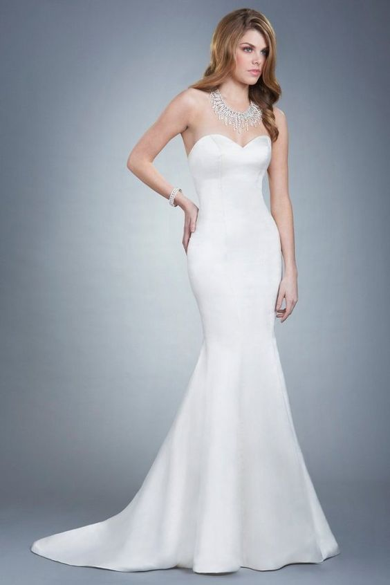 Allie is a glamorous silk duchess gown that hugs the figure perfectly. This dress features keepsake genuine pearl buttons, a trumpet silhouette and a chapel length train. Olia Zavozina