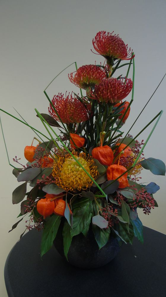 This Halloween spook-tacular includes Leucospermums, Aralia and Physalis!! Check out more ideas on our blog or visit our website! — at Triangle Nursery - Wholesale Flowers - Wholesale Wedding Flowers.