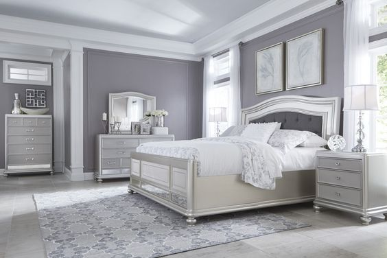 The Coralayne upholstered queen bed by Ashley Furniture allures with the glitz and glam of the Hollywood elite. The frame's chic metallic tone brings the flair you've been dreaming of. Featuring an arched headboard with double frame and a button tufted cushion in a dark textured gray fabric as well as textured and mirror paneling on the footboard, the Coralayne is a fashion A-lister.