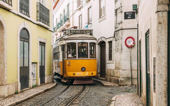 Eine Straßenbahn schlängelt sich an Häusern vorbei © Shutterstock.com