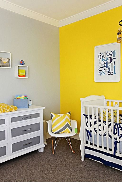 Bold yellow theme unifies this nursery, with pillows reflecting yellow wall. White wood crib and dresser with grey drawers over brown carpet...