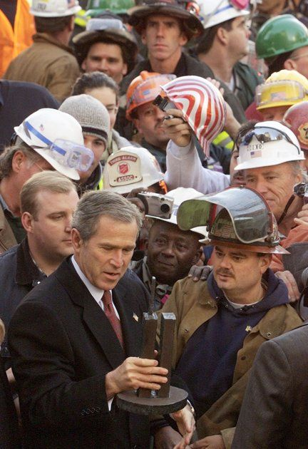 U.S. President George W. Bush looks at a model of the World Trade Center as he meets with rescuers at Ground Zero at the World Trade Center after a memorial service in New York, November 11, 2001.