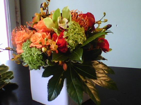 Modern floral arrangement with protea, cymbidium orchids, miracle roses, mokara orchids, and tropical foliage.