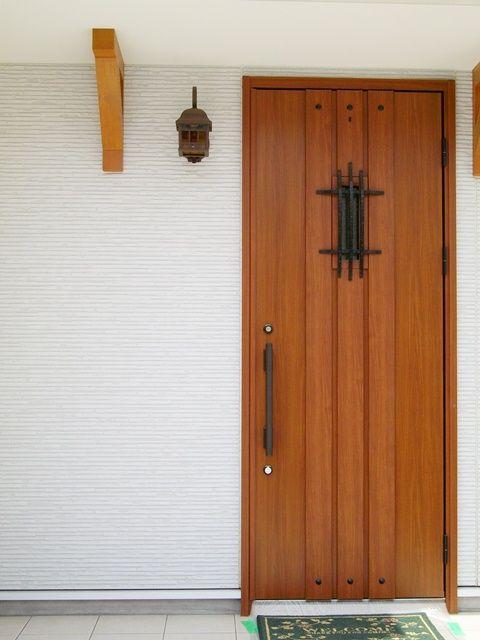 アイアン飾りがついた玄関ドアとアンティーク風なポーチライト 株式